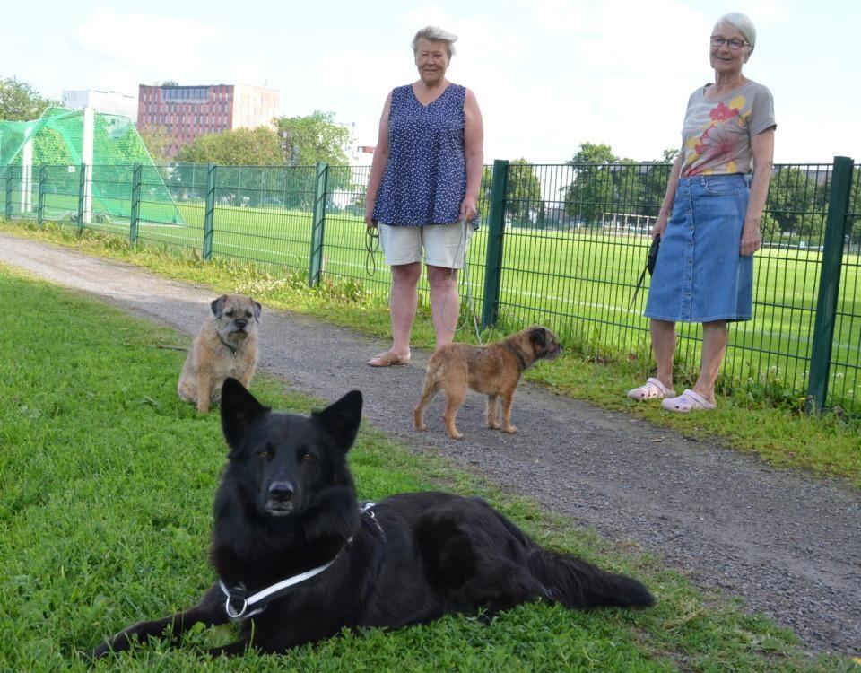 Två damer står på en gräsmatta med sina tre hundar, två små och en större svart