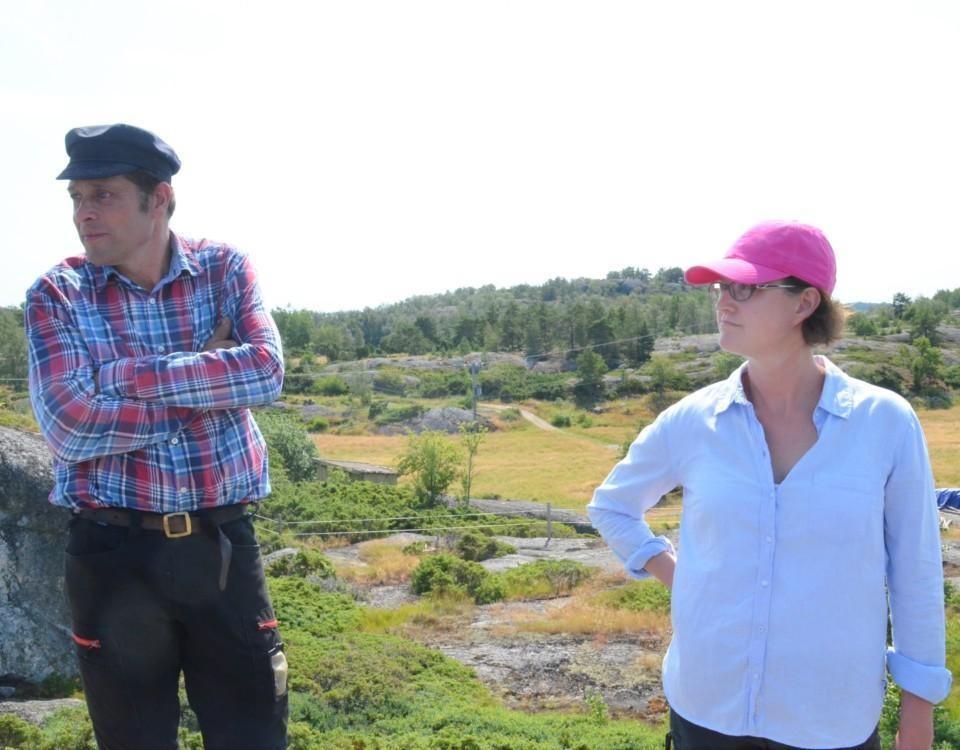 Mann och kvinna står på berg, bakom dem syns en äng