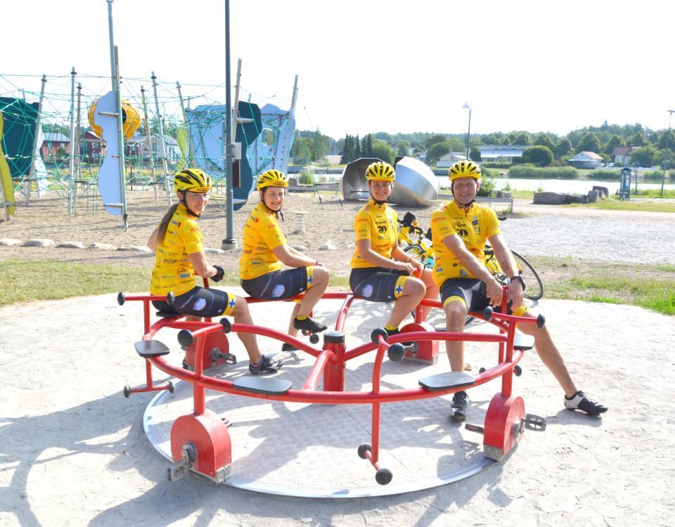 fyra gulklädda cyklister i en barnkarusell