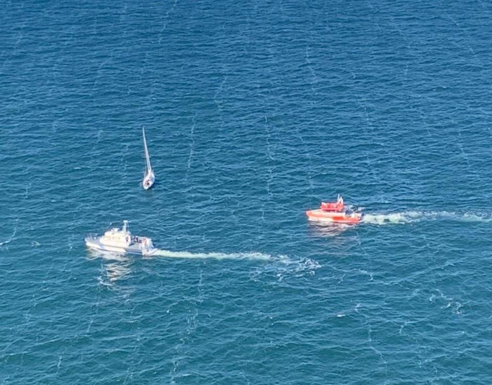 En segelbåt ute till havs med två patrullbåtar i närheten.
