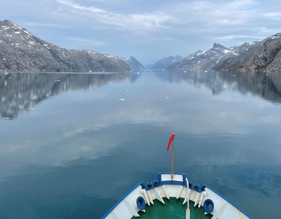 Fören på en båt som färdas i en fjord. Havsytan är glasblank.