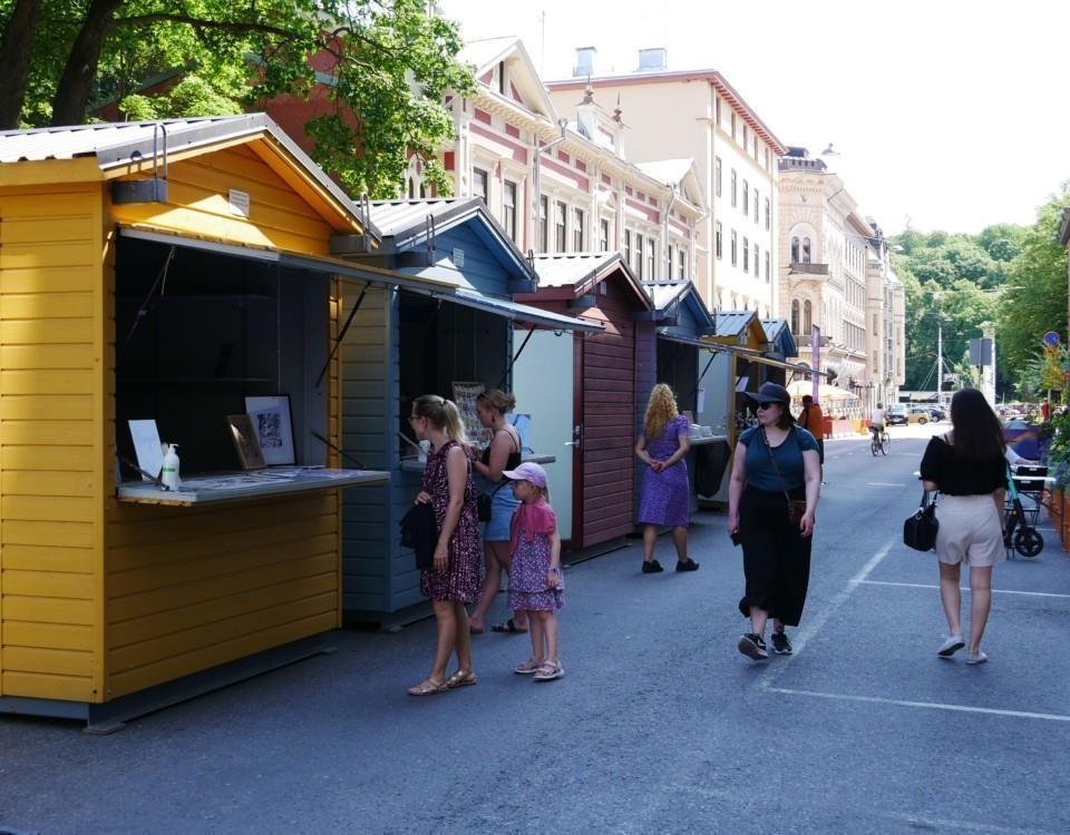 En rad med färgglada försäljningsstånd och människor som strosar runt på en sommargata.