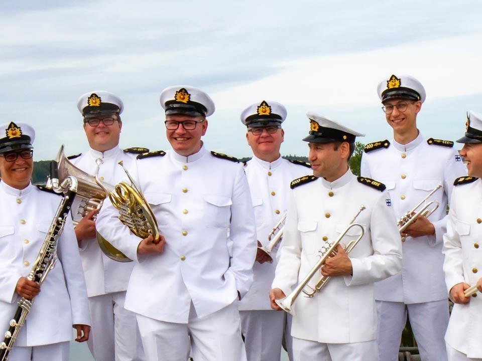 En rad med män iklädda flottans vita uniformer håller i olika blåsinstrument.