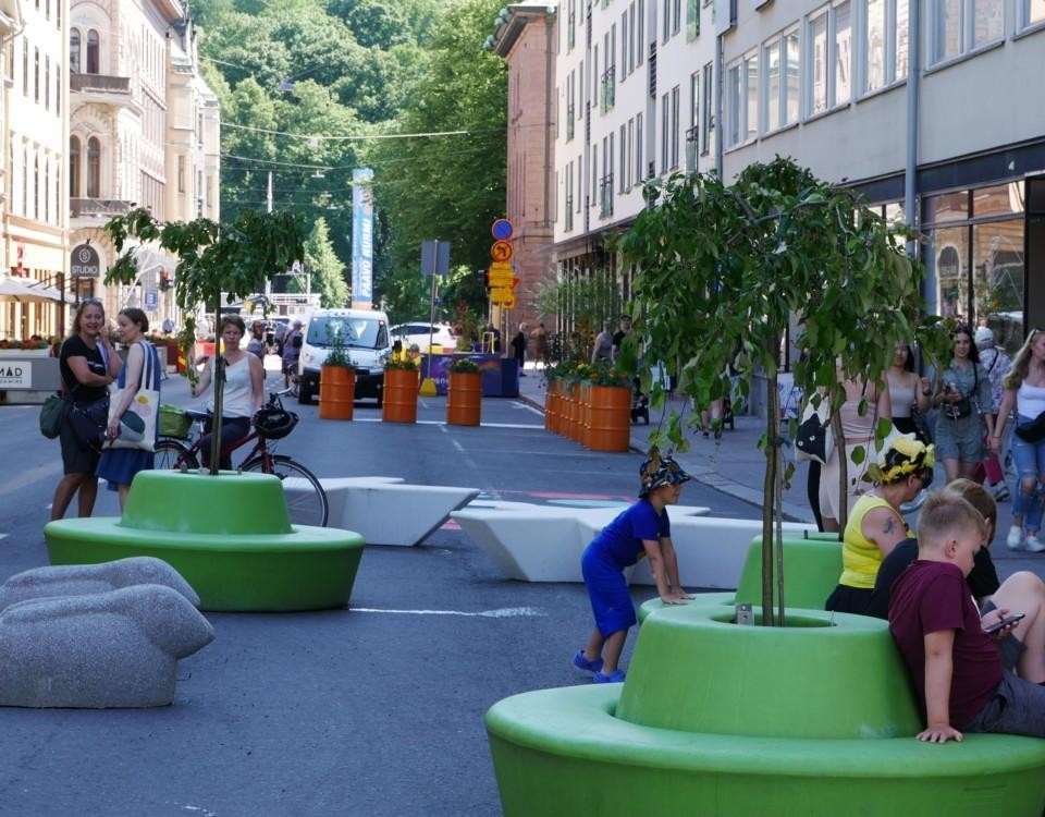 Gågata i centrum av staden, många människor går av och annfärggranna bänkar och växter