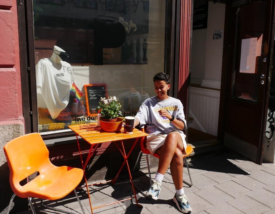 En ung kvinna sitter i solskenet utanför en second hand-affär.
