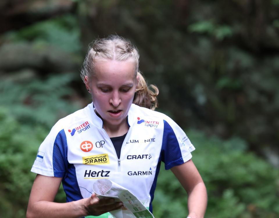 Ung kvinna springer med karta i handen.