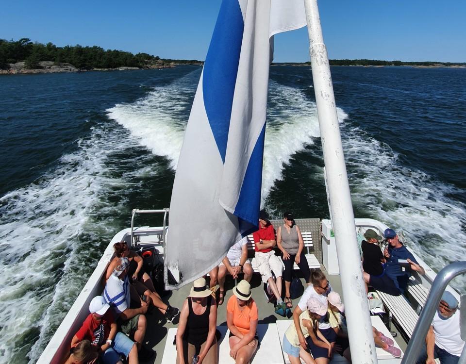människor sitter i aktern på charterbåt en varm sommardag