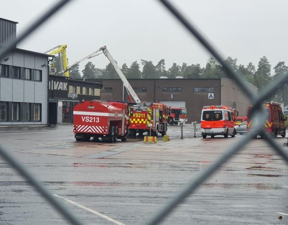 Flera brandbilar utanför en produktionsanläggning. Regnigt och grått.