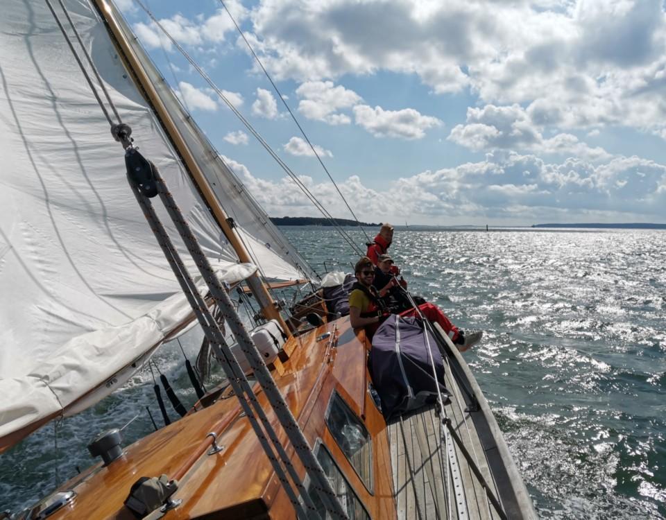 Människor som sitter på däck ombord på en seglande båt.