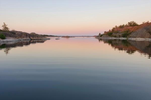 Spegelblankt hav med öar.