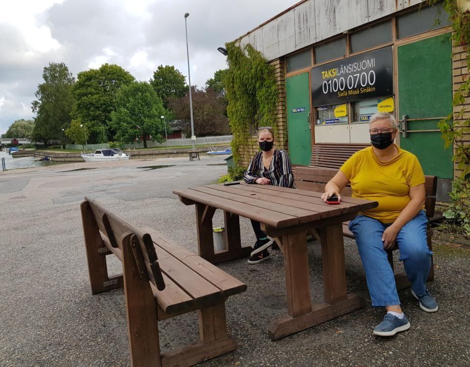 två kvinnor sitter vid ett träbord framför ett slitet hus