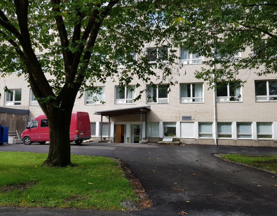 träd i förgrunden, grå skolbyggnad i tegel i bakgrunden, röd skåpbil till vänster
