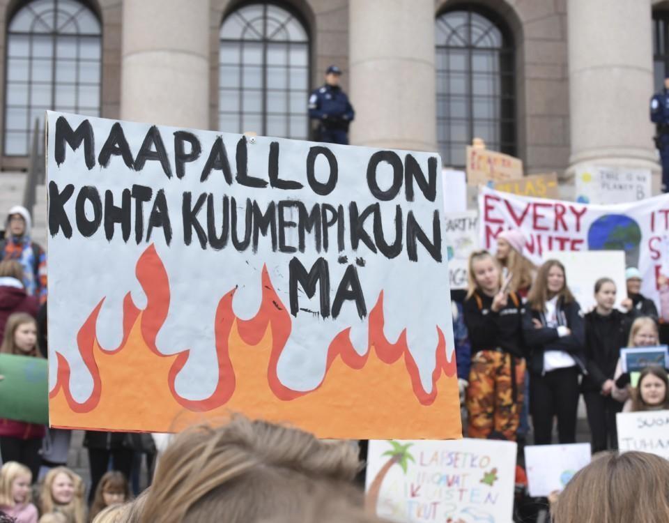 Människor som demonstrerar med ett stort plakat.