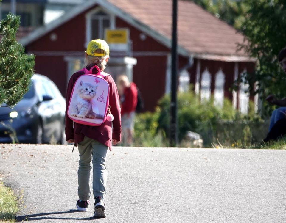 Ett barn med skolväska på ryggen.