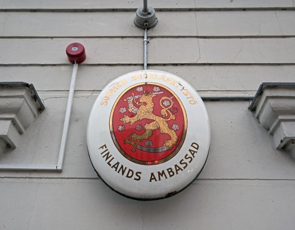 Ett märke med texten Finlands ambassad på väggen.