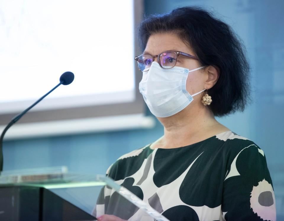 kvinna med munskydd vid en talarstol