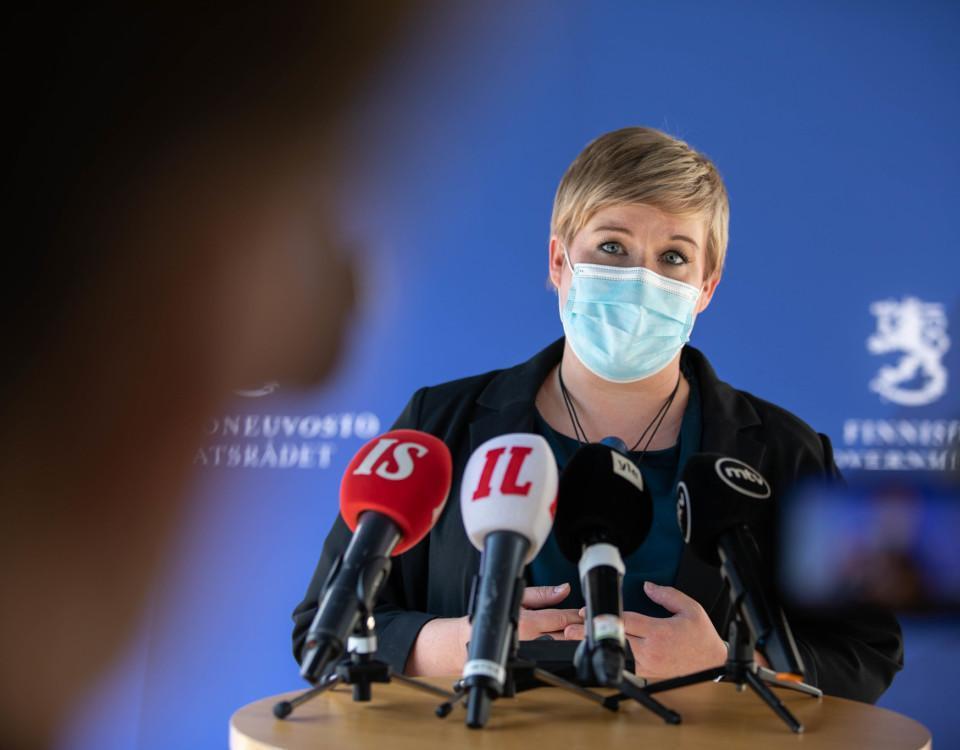 kvinna i munskydd framför mikrofoner