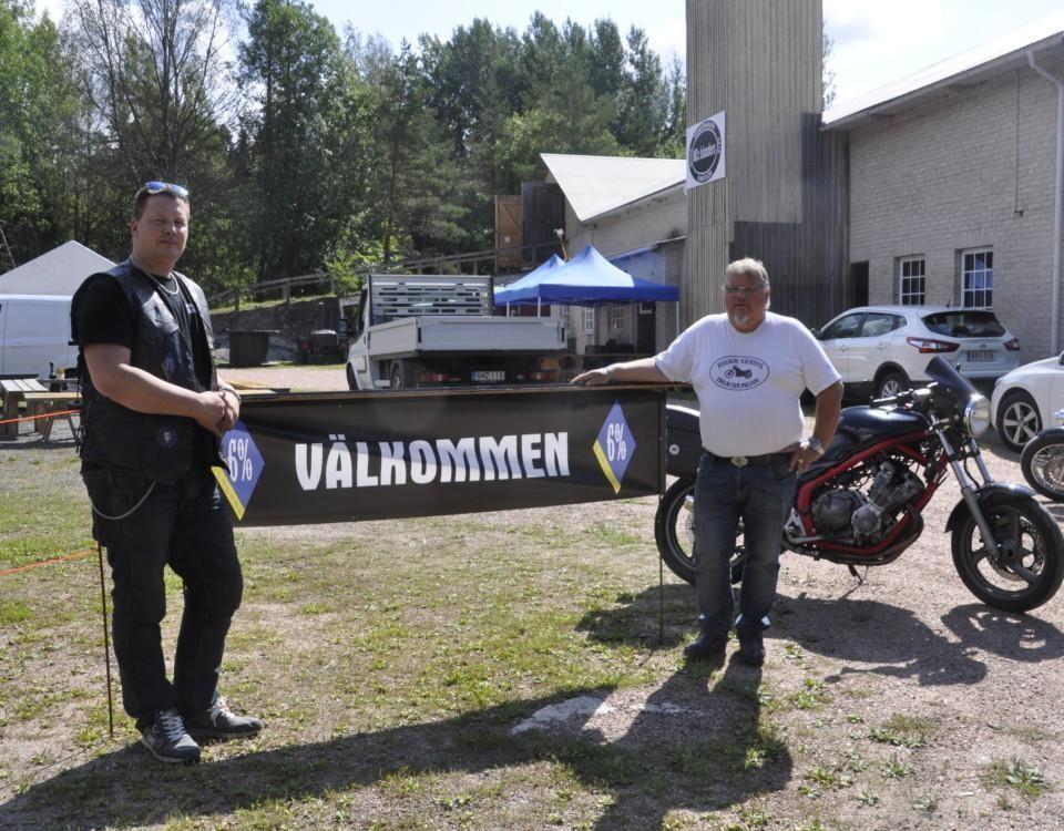 Två män vid en stor välkommen skylt, utanför en mc-klubblokal