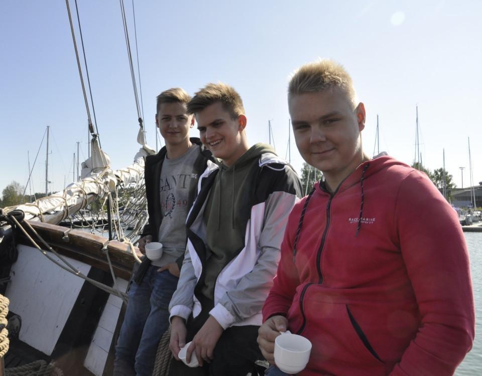 tre pojkar på en segelskuta