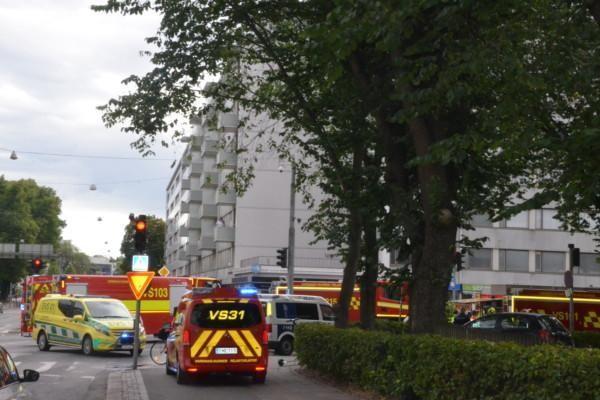 Ambulanser och brandbilar på en gata.