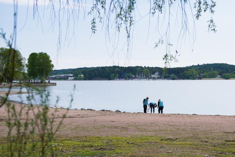 en strand, tre personer i bakgrunden