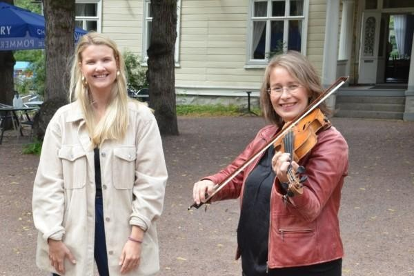 Två kvinnor står framför ett hus, en av dem spelar fiol