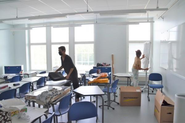 Två kvinnor packar upp i ett klassrum