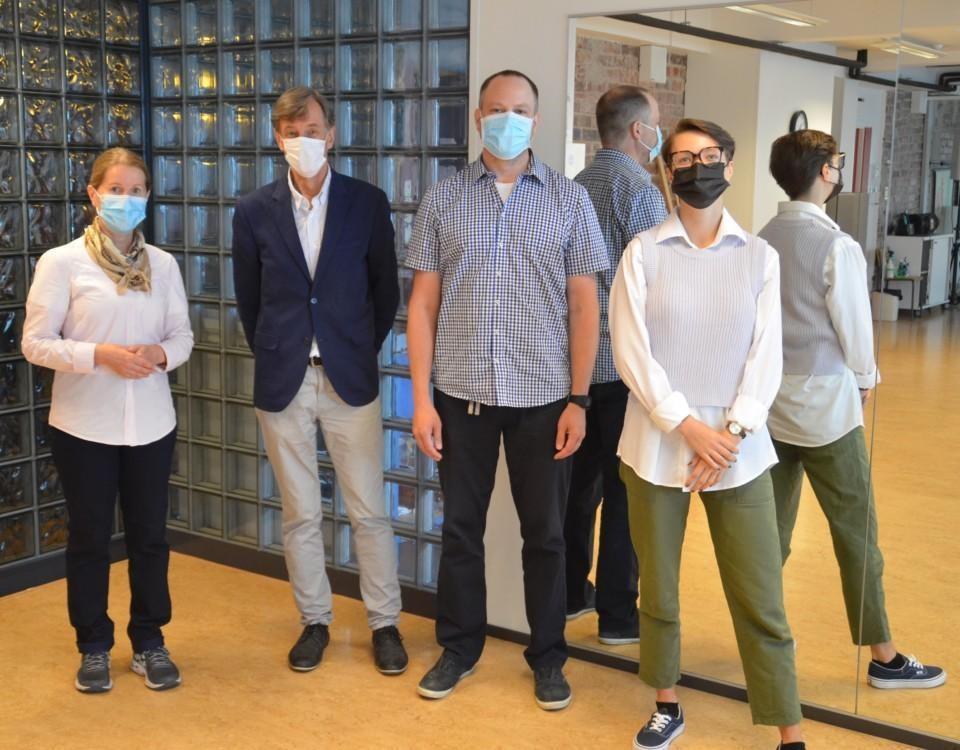 Fyra personer, en man och en kvinna står i ett ru. De har ansiktsmasker