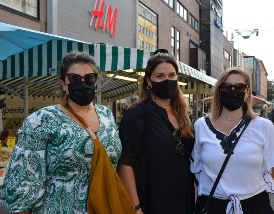 Tre kvinnor på en gågata.