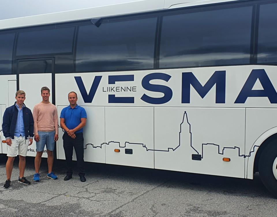 Tre män står framför en buss