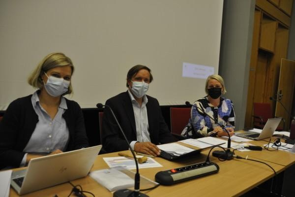 tre personer med munskydd vid ett bord