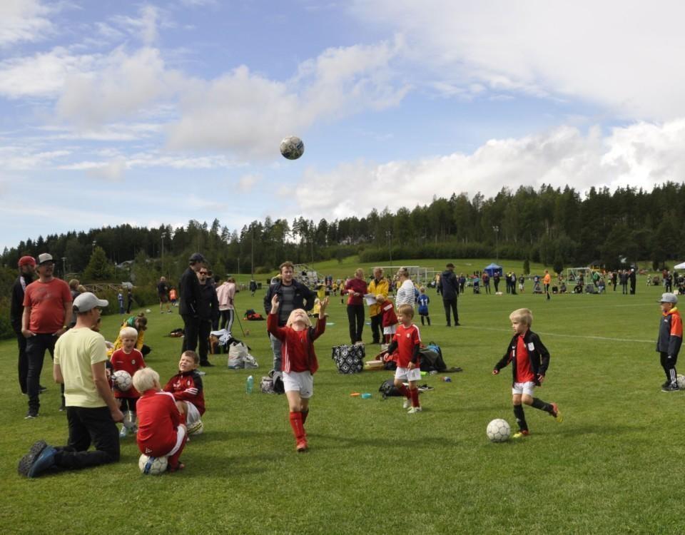 Stor grön plan med många små fotbollsspelare