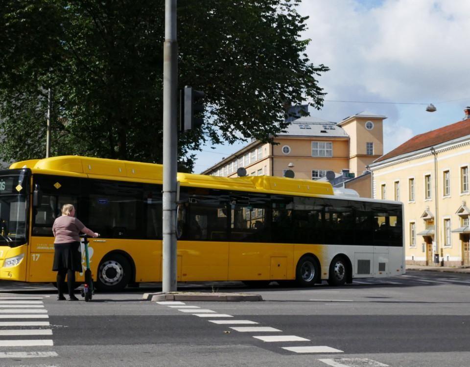 en buss gör en sväng och en person med elsparkcykel väntar på att gå över vägen