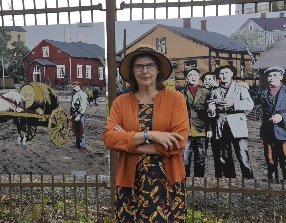 Dam framför ett långt konstverk på ett staket