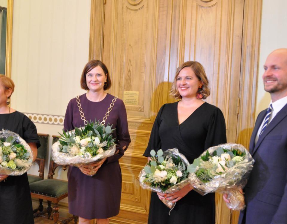 Tre kvinnor och en man med blommor i händerna