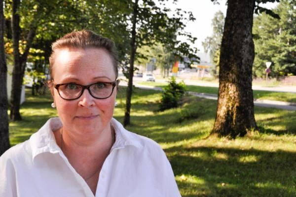 En kvinna med glasögon står i en park