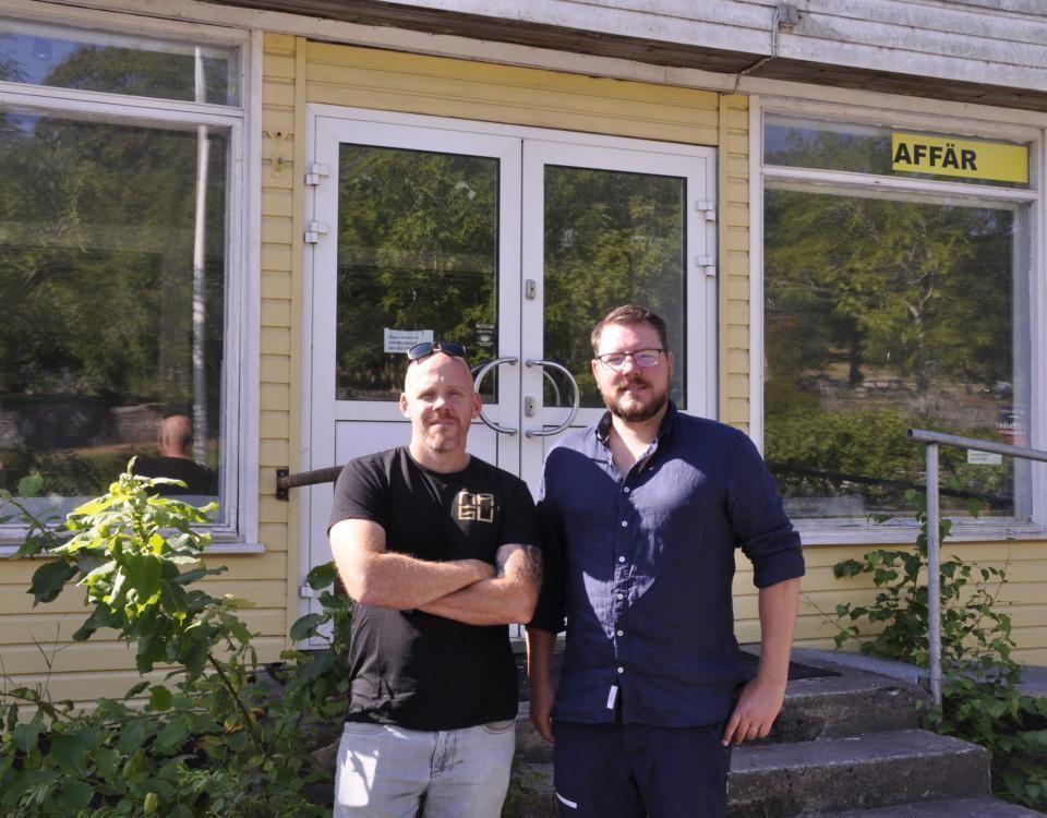 Två män står utanför ett hus