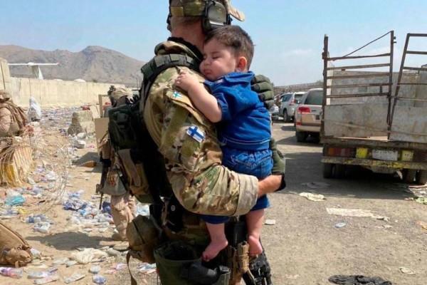 en soldat bär ett barn