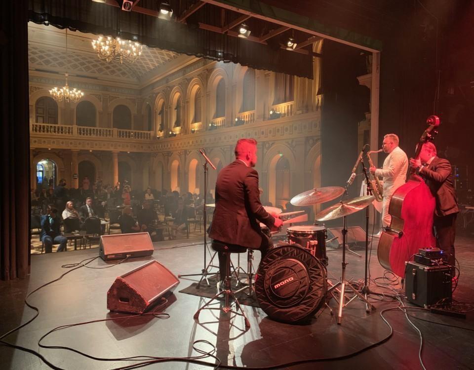 Sven med musiker. Publik i bakgrunden