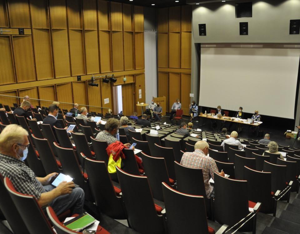 auditorium med folk fotade bakifrån som sitter långt ifrån varandra