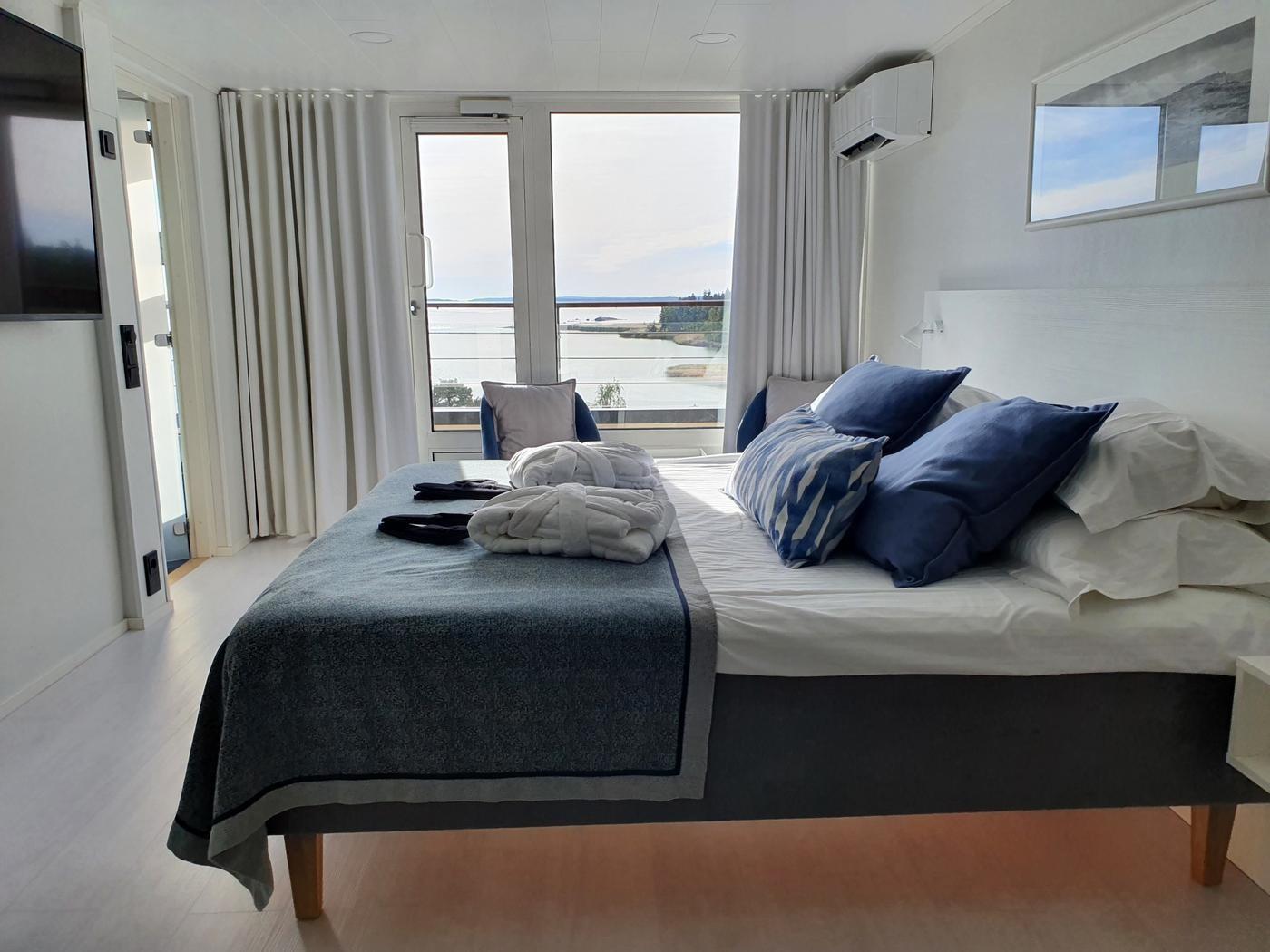 En hotellsäng med fin utsikt över havet.