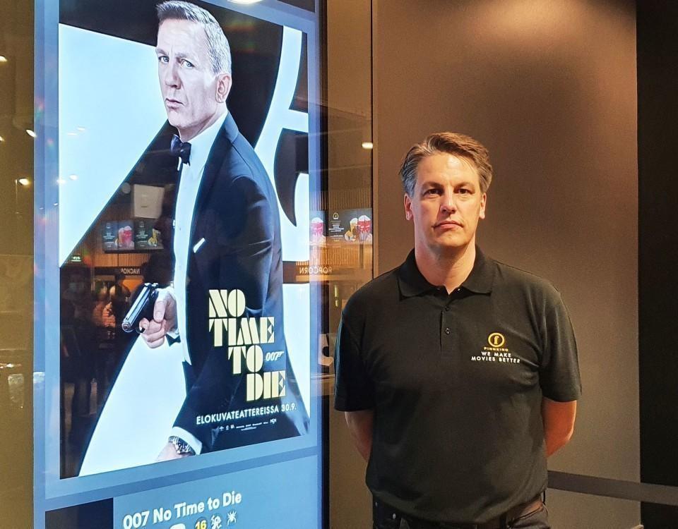 Kari korhonen framför en reklamskylt med James Bond.
