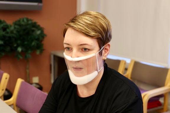 Kvinna med genomskinligt munskydd.
