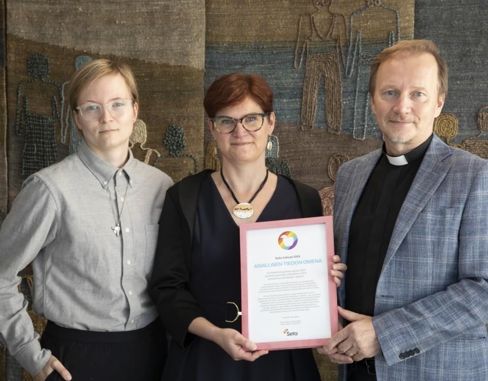 Tre personer med ett diplom.