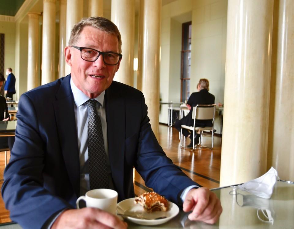 man sitter vid kaffebord i riksdagens kafferum