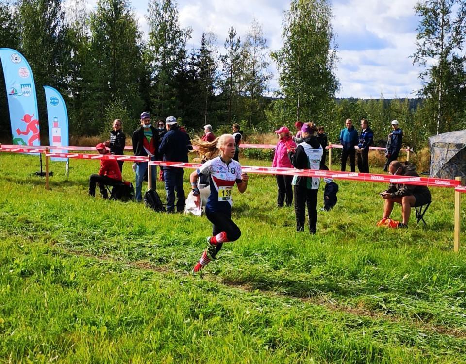 Kvinna springer i mål i en orienteringstävling.