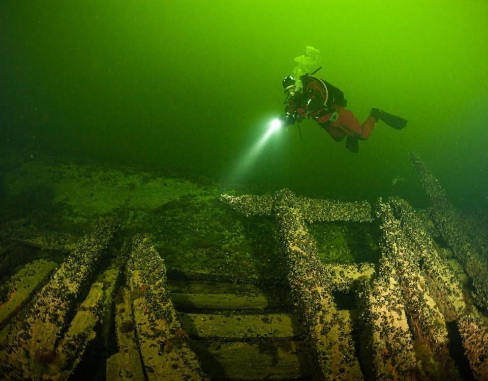 Bild av dykare som dyker vid ett vrak med en ficklampa.