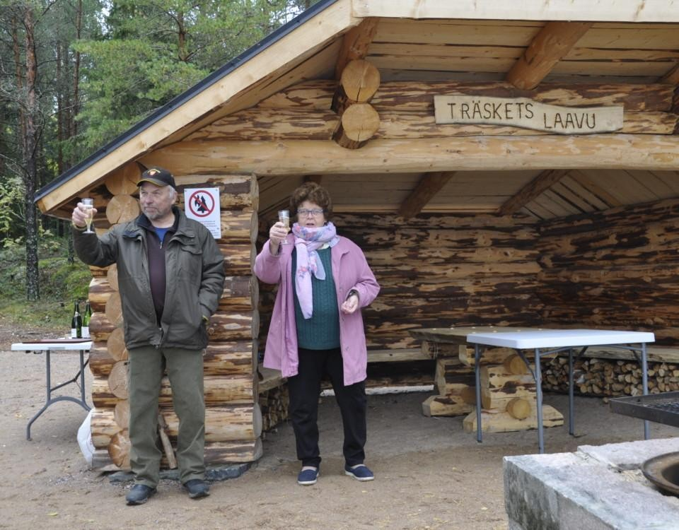 två personer skålar vid ett vindskydd