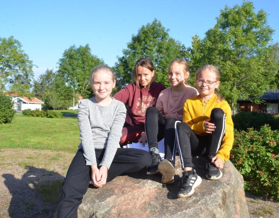 Barn som sitter på en sten.