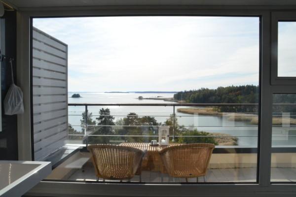 Två stolar på en balkong med utsikt över havet.